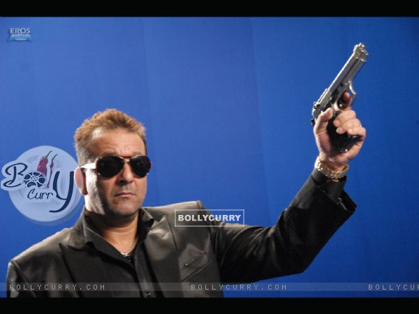 Sanjay Dutt standing with a rifle