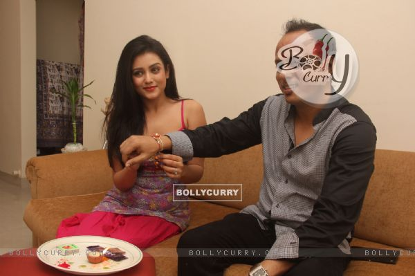 Mishti ties a rakhi to het brother